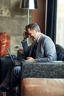 Smiling businessman using laptop and smartphone in hotel lobby - p300m2170936 by Zeljko Dangubic