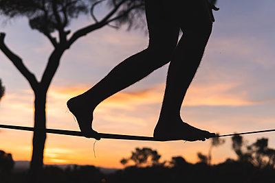 Man walking on tightrope during sunset - p300m2293557 by Josu Acosta