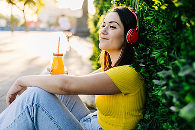 Smiling woman with juice bottle listening music through headphones while leaning on hedge - p300m2293947 by Xavier Lorenzo