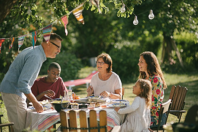 Senior man and granddaughter talking while having lunch with family in backyard during party - p426m2036598 by Maskot