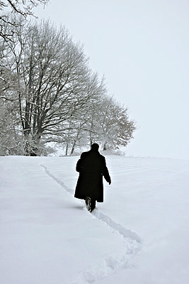 Man running in snow - p476m971241 by Ilona Wellmann
