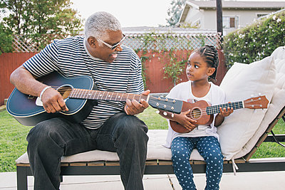 African American grandfather teaching granddaughter to play guitar - p555m1408328 by Hello Lovely