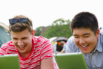 Laughing Teenage Boys Using Tablets - p669m806416 by Jutta Klee photography
