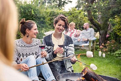 Friends roasting marshmallows - p788m1165408 by Lisa Krechting