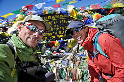 Trekkers looking at camera near prayer flags, Thorung La, Nepal - p92412104 by HagePhoto