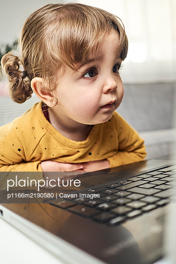 Adorable baby with a laptop - p1166m2190580 by Cavan Images
