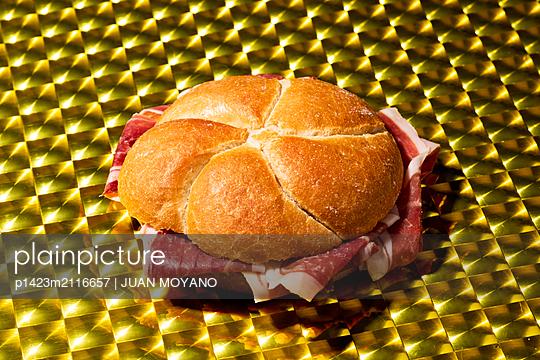 Serrano ham sandwich on a golden surface - p1423m2116657 by JUAN MOYANO