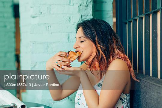 Woman eating croissant in coffee shop - p300m1587413 von Javier Pardina