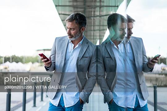 Businessman leaning against glass facade using smartphone - p300m2012298 von VITTA GALLERY