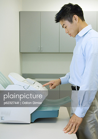 Male office worker using fax machine