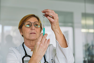 Doctor preparing a vaccine for patient - p300m2180529 by Mareen Fischinger