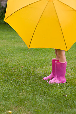 Young girl legs under umbrella - p6691083 by Julian Winslow
