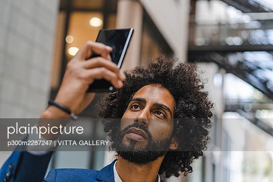 Businessman taking selfie through smart phone - p300m2287247 by VITTA GALLERY