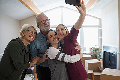 Parents helping affectionate lesbian couple move into new house, taking selfie - p1192m1560018 by Hero Images