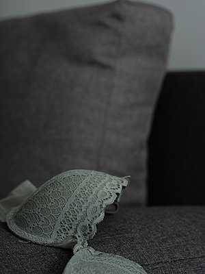 Bra on a couch  - p1383m2262382 by Wolfgang Steiner