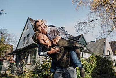Man giving his wife a piggyback ride in garden - p300m2166635 by Kniel Synnatzschke