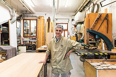 Smiling male carpenter with hand on hip at workshop - p300m2293674 by Eugenio Marongiu