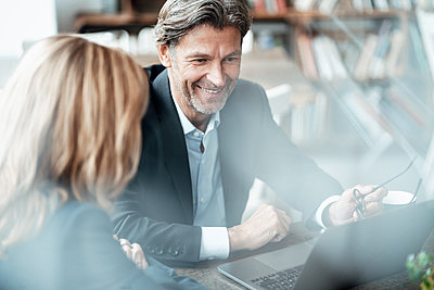 Smiling mature businessman discussing with female colleague over laptop sitting in cafe - p300m2293768 by Joseffson