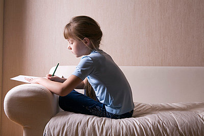 portrait of young girl sitting on sofa and drawing on paper - p3164844f by Vladimir Godnik