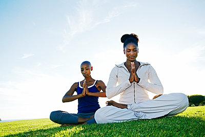 Women meditating in park - p555m1411325 by Peathegee Inc
