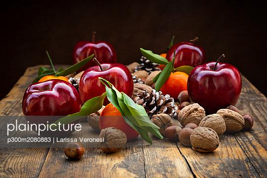 Red apples, tangerines, hazelnuts, walnuts and pine cones on dark wood - p300m2080883 by Larissa Veronesi