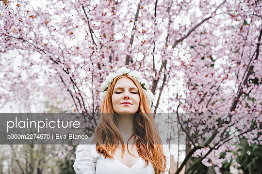 Young woman with eyes closed wearing white flower tiara standing in front of almond tree - p300m2274570 by Eva Blanco
