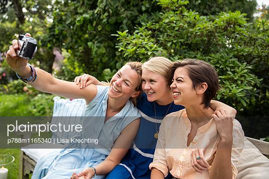 Freundinnen machen ein Selfie auf der Gartenbank - p788m1165340 von Lisa Krechting