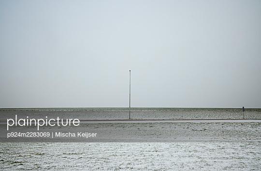 Netherlands, Friesland, Zurich, Pole in snow covered field - p924m2283069 by Mischa Keijser