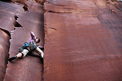 Low angle view of hiker climbing cliff - p1166m1174297 by Cavan Images