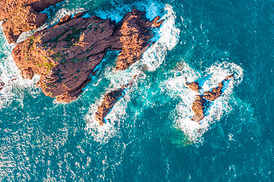 Aerial view of rock formations in sea during sunny day - p1166m2040467 by Cavan Images