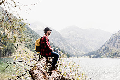 Austria, Tyrol, Alps, hiker sitting on tree trunk at mountain lake - p300m1505354 by Uwe Umstätter
