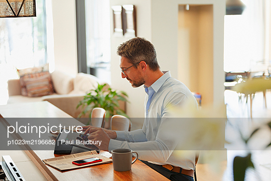 Businessman using digital tablet, working from home in kitchen - p1023m2196682 by Paul Bradbury