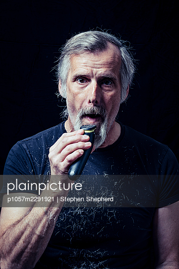 A middle aged man shaving off his grey beard that he grew duyring the lockdown caused by the covid-19 pandemic. - p1057m2291921 by Stephen Shepherd