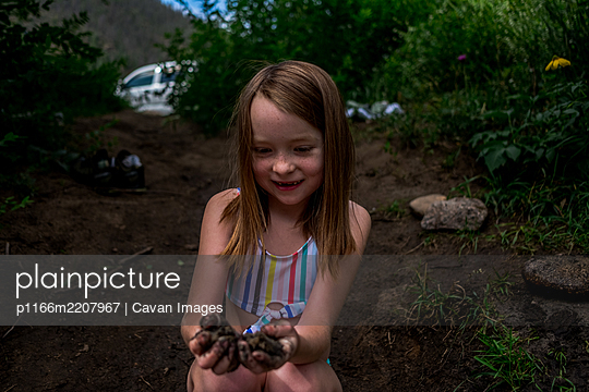 Center portrait of young girl with muddy hands on the bank of a river - p1166m2207967 by Cavan Images