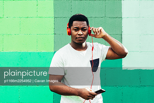 Afro American black boy on green wall background . Listening to music with headphones and mobile phone. - p1166m2254952 by Cavan Images
