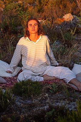 Teenage boy sits on blanket in a meadow - p1640m2245877 by Holly & John