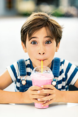 Portrait of little girl drinking strawberry milkshake at pavement cafe - p300m2029756 by Javier Sánchez Mingorance
