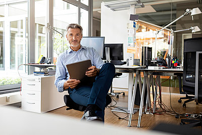 Confident entrepreneur with digital tablet sitting at open plan office - p300m2257106 by Peter Scholl