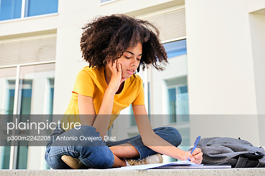Curly hair student studying while sitting at university campus - p300m2242208 by Antonio Ovejero Diaz