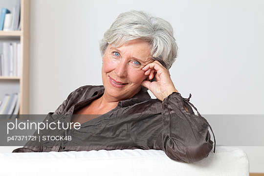 Zufriedene Seniorin auf der Couch - p4737172f von Stock4B