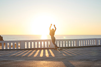 Female longboarder on boardwalk at sunset  - p1124m1503656 by Willing-Holtz