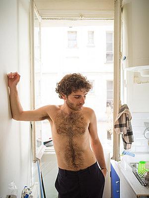 Man standing in front of open window - p1267m2090174 by Wolf Meier