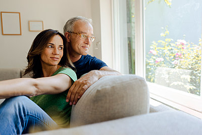 Smiling mature couple sitting on couch at home looking out of window - p300m2029802 by Kniel Synnatzschke