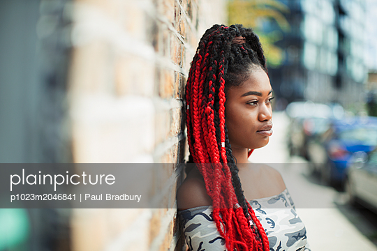 Confident young woman with red braids looking away on urban street - p1023m2046841 by Paul Bradbury