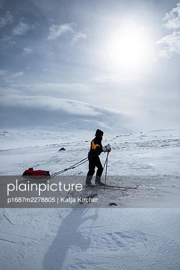Man on backcountry skiing hike pulling a ski pulk (toboggan) - p1687m2278805 by Katja Kircher