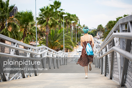 Spain, back view of young woman with blue dyed hair with backpack running on a bridge - p300m2069547 by Eloisa Ramos