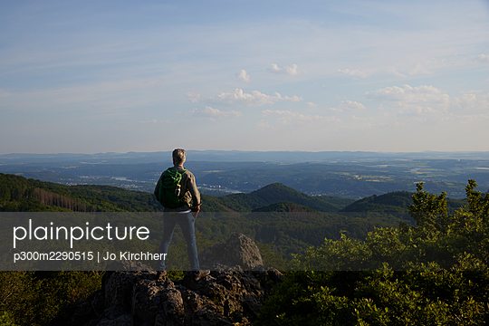 Male backpacker looking at scenic landscape while standing on top of mountain - p300m2290515 by Jo Kirchherr