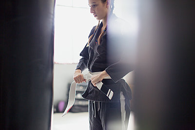 Young woman tying judo belt in gym - p1023m1506449 by Sam Edwards