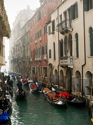A view of a narrow canal crowded with boats and traditional gondolas, with historic buildings lining the waterfront. - p1100m991389f by Mint Images