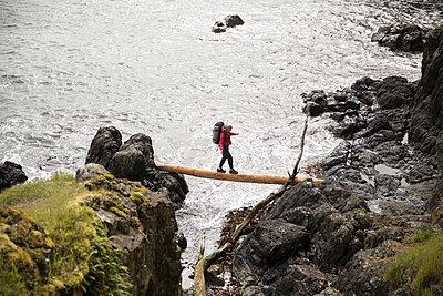 Female backpacker crossing fallen log between cliffs overlooking ocean - p1192m2000406 by Hero Images